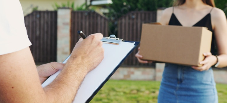 A woman handing a box off to someone with a clipboard.