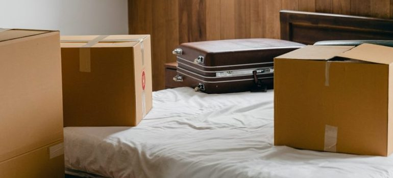 A suitcase on a bed next to some boxes.
