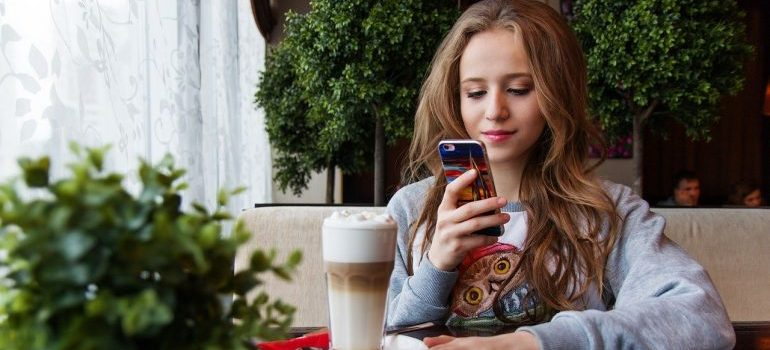 A girl in a coffee shop holding a phone.
