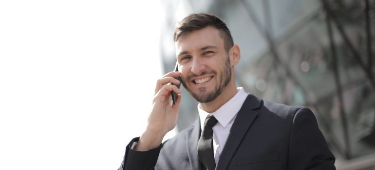 Smiling businessman talking on the phone with commercial movers NYC