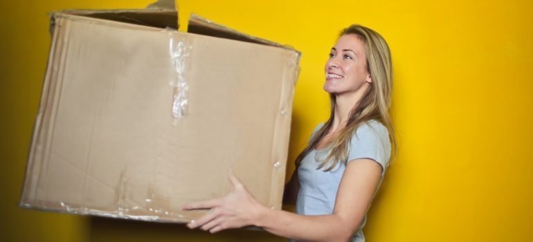 A woman holding a cardboard box.