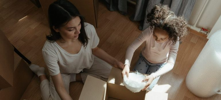 mother and daughter packing a box