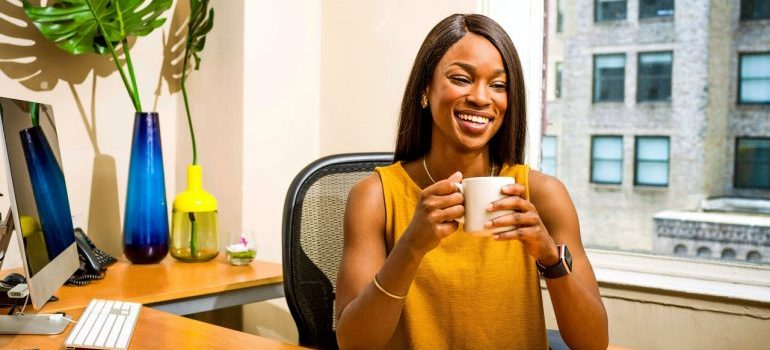 Woman holding a mug in an office.