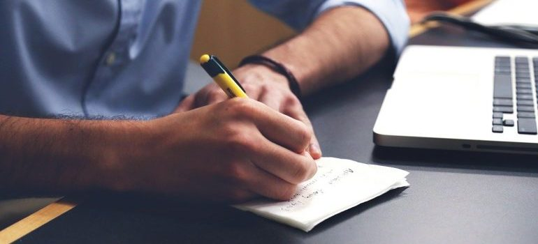 A man writing in a notebook.
